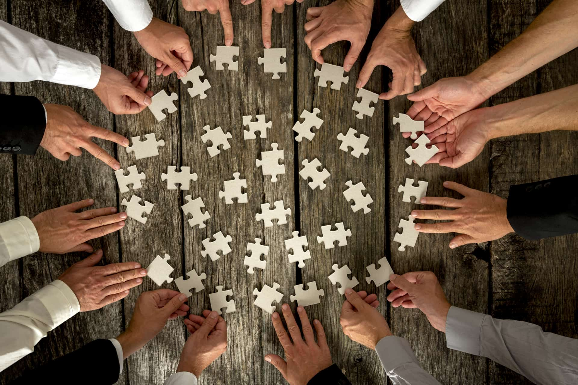 Hands Holding Puzzle Pieces on Table